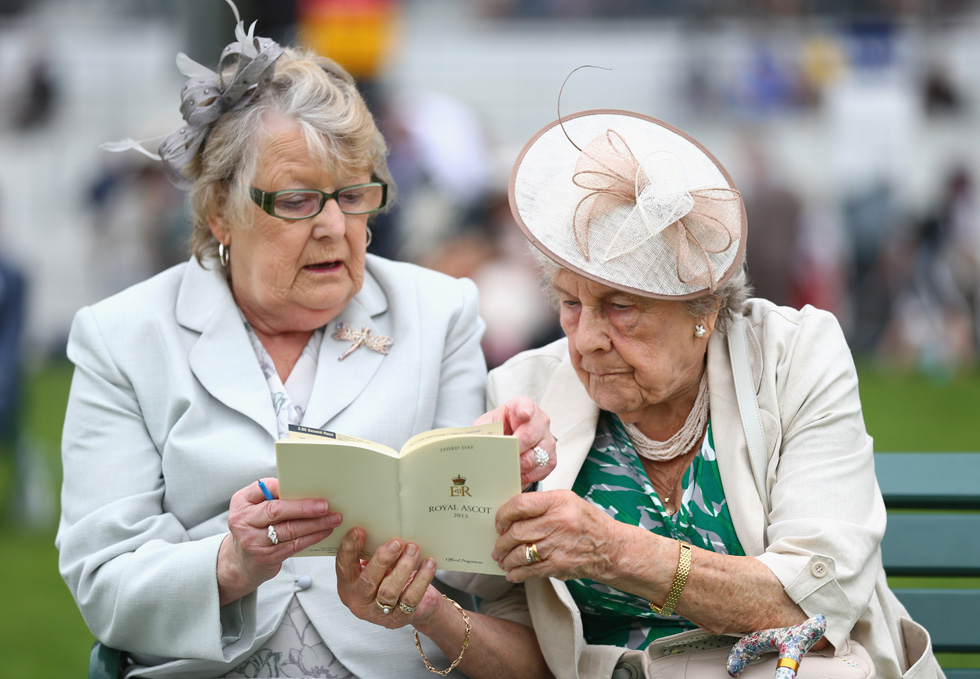 Racegoers study the race card on Ladies' Day during day three of Royal Ascot at Ascot Racecourse on June 20, 2013 in Ascot, England. Paul Gilham/Getty Images