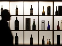 A visitor is silhouetted as he walks past bottles of wine displayed at Vinexpo, the world's largest wine fair, in Bordeaux, France, June 18, 2013.  REUTERS/Regis Duvignau