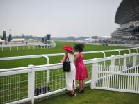 Women view the course before races begin on the third day of Royal Ascot, in Berkshire, west of London, on June 20, 2013. The five-day meeting is one of the highlights of the horse racing calendar. AFP PHOTO/CARL COURT/AFP/Getty