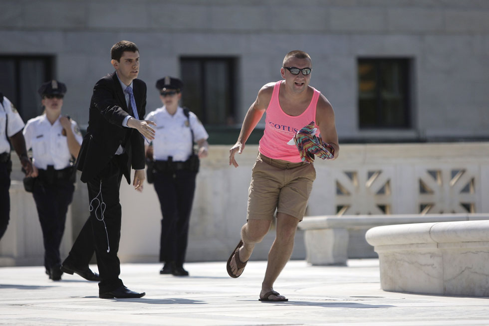 A man runs with the printed copy of the U.S. Supreme Court's ruling against the federal Defense of Marriage Act (DOMA), outside the court in Washington, June 26, 2013. REUTERS/Jonathan Ernst