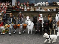 A white poodle runs past plaster animal sculptures displayed at a road-side shop near the village of Kolesov, Czech Republic, June 28, 2013. The kitsch figurines of various animals, dwarfs and different characters are popular garden ornaments. REUTERS/Petr Josek