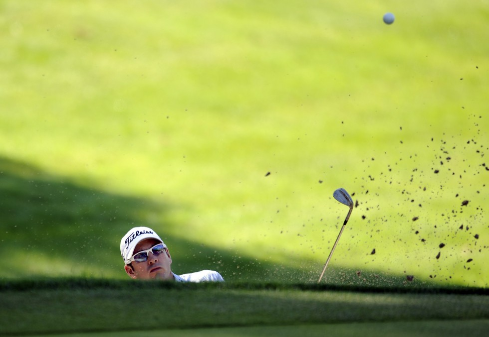 Ben Curtis hits out of the greenside bunker on the 18th hole during the opening round of the Travelers Championship. Photo by JOHN WOIKE|woike@courant.com