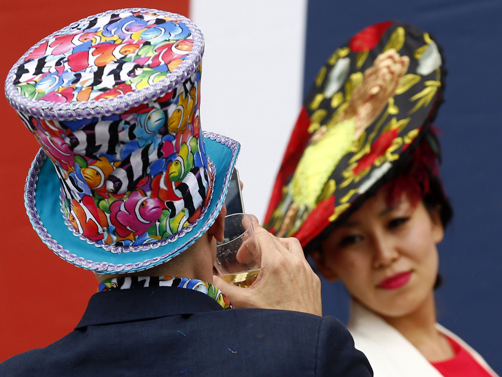 Attendees of the Royal Ascot horse racing festival in Ascot, England, pose for photographs on the first day of the festival, June 18, 2013. Horse racing started at the famous Berkshire course in 1711.  REUTERS/Darren Staples