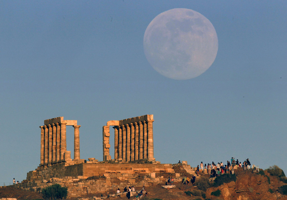 The Supermoon rises over the temple of Poseidon, the ancient Greek god of the seas, as tourists enjoy the sunset in Cape Sounion, Greece, June 22, 2013. The moon reached its full stage on Sunday, 6/23 REUTERS/Yannis Behrakis (
