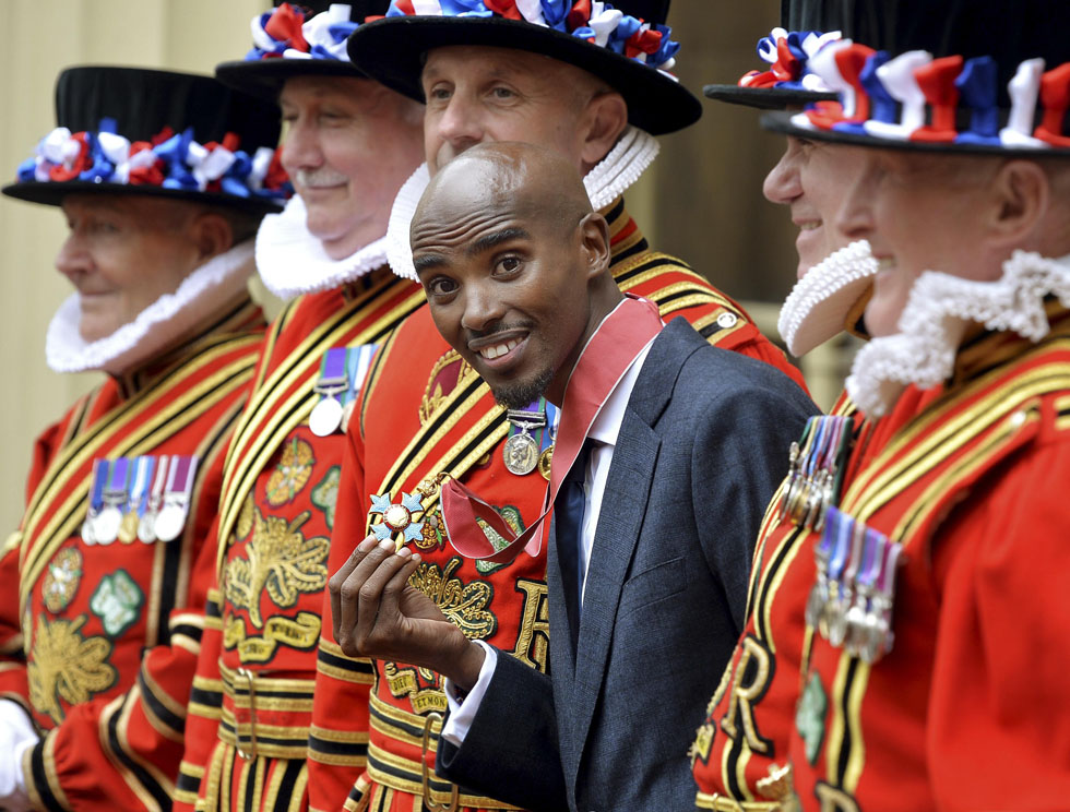 Britain's double Olympic champion, Mo Farah, poses with his Commander of the Order of the British Empire medal, after being presented with it by Prince Charles during a ceremony at Buckingham Palace in London, June 28, 2013.    REUTERS/John Stillwell/pool