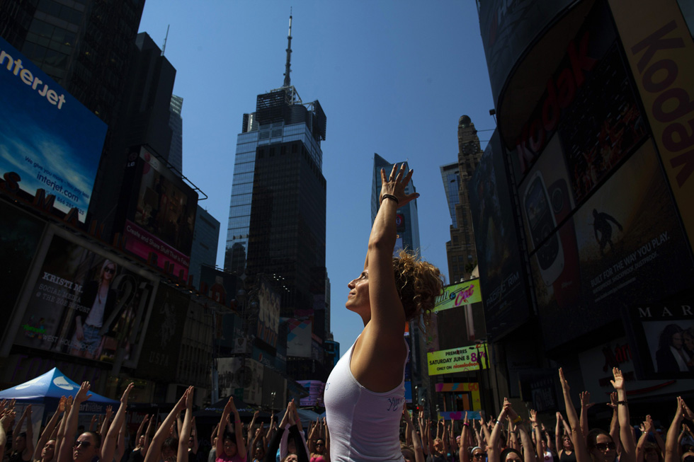 "People take part in a group yoga practice on the morning of the summer solstice in New York's Times Square, June 21, 2013. The ""Solstice in Times Square"" event brought out thousands of participants to celebrate the year's longest day in New York. REUTERS/Eric Thayer"