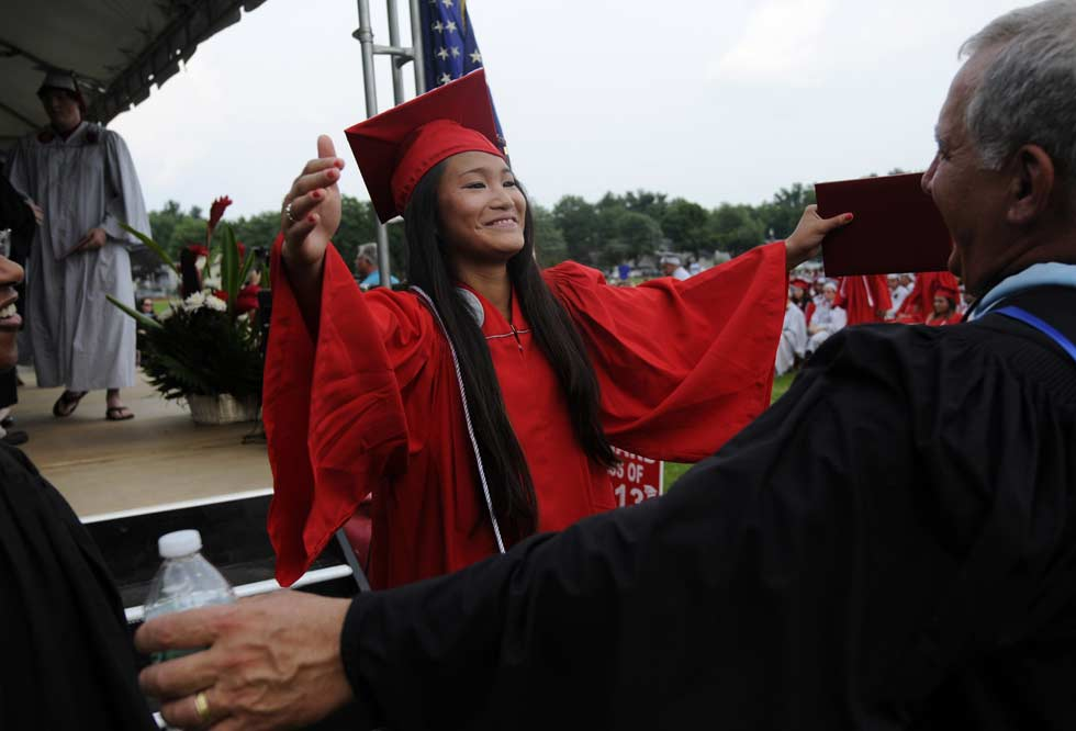 -  6.24.2013  - West Hartford, CT;  Conard High School graduate Alison Dizon gets a hug from assistant principal Matt Pace after she received her diploma during ceremonies in the field behind the West Hartford school Monday.