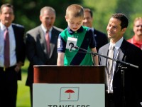 Jimmy Canton (right) smiles at Cameron Merritt, 11, as Merritt addresses the crowd at opening ceremonies at the 2013 Travelers Championship Monday morning at TPC River Highlands in Cromwell.  Canton is  CEO of the Hole in the Wall Gang Camp, a free camp for seriously ill children in Ashford, where Merritt is a camper.  The camp is one of the tournament's beneficiaries.