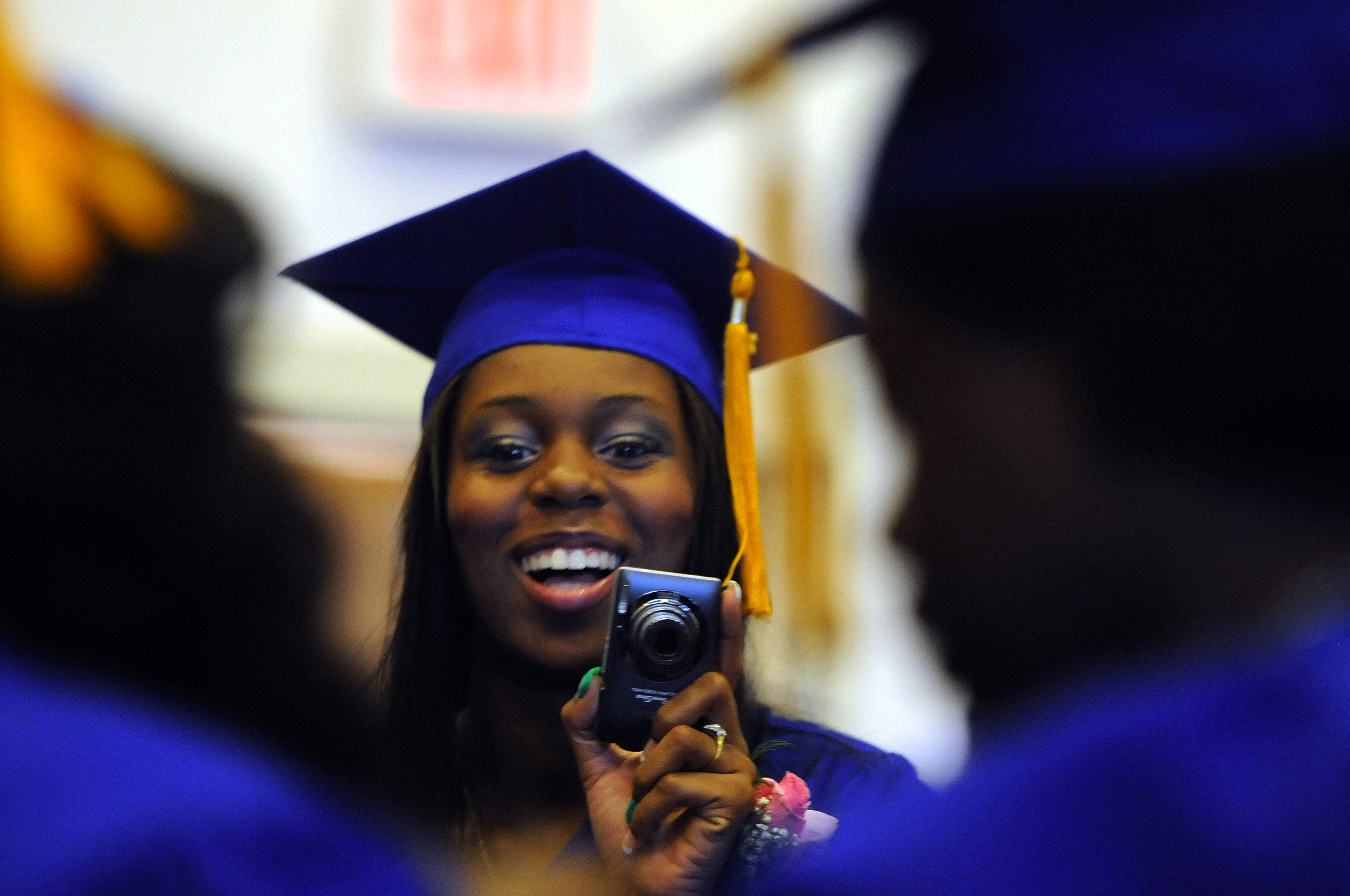Lichelle Burke, 19, takes photos of her friends before the ceremonies began.