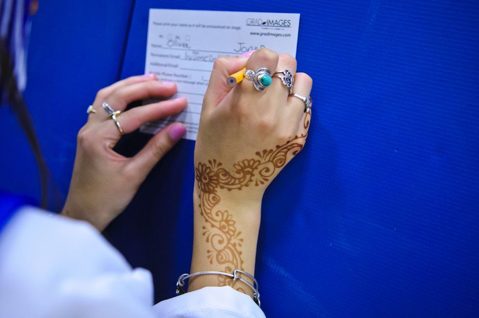2013.06.24 - West Hartford, CT - Her hand decorated with henna at a graduation party, Hall High School graduate Olivia Jones fills out paper work prior to the school's graduation ceremony.  Photograph by Mark Mirko | mmirko@courant.com