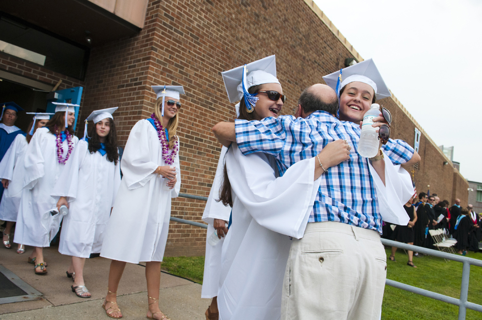 2013.06.24 - West Hartford, CT - Hall High School music teacher John Mastroianni stops conducting the school's band to hug graduates (L-R) Paulina and Maggie Rowe as they process in the school's commencement ceremony. Photograph by Mark Mirko | mmirko@courant.com