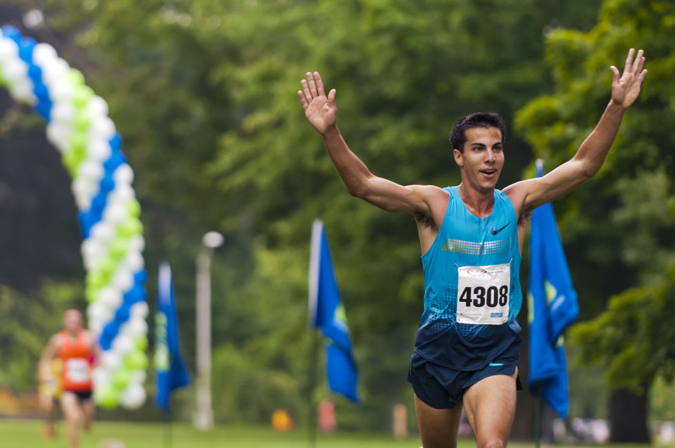 2013.06.30 - Middletown, CT - Glastonbury Olympian Donn Cabral, who won the Legends Race with a time of 0:19:28, raises his arms in victory as he approaches the finish line. Photograph by Mark Mirko | mmirko@courant.com