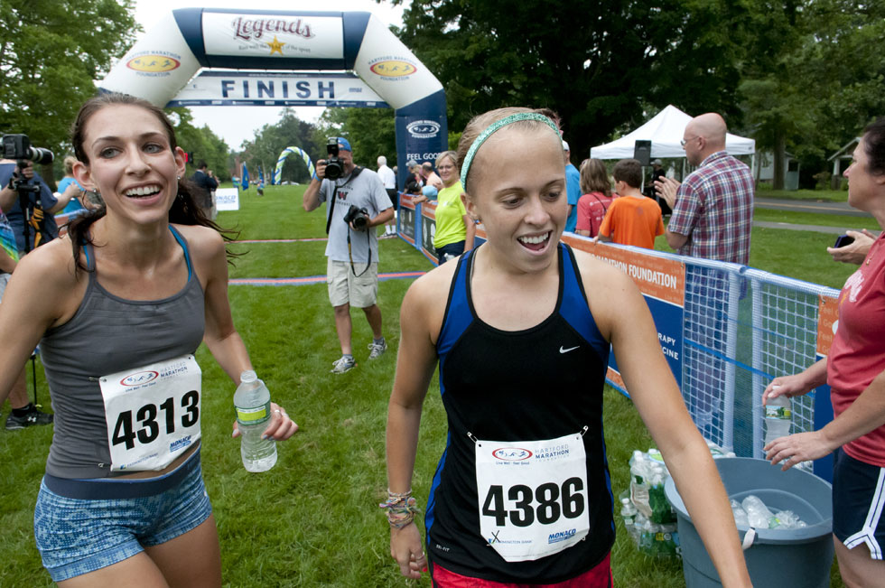 2013.06.30 - Middletown, CT - Katie Matthews, of Rocky Hill, who won the women's division of Legends Race with a time of 00:22:02, greets UConn runner Lauern Sara raises her arms in victory after she crosses the finish line of the four-mile race with a time of 00:22:14. Matthews finished 10th overall and Sara finished 11th overall. Photograph by Mark Mirko | mmirko@courant.com