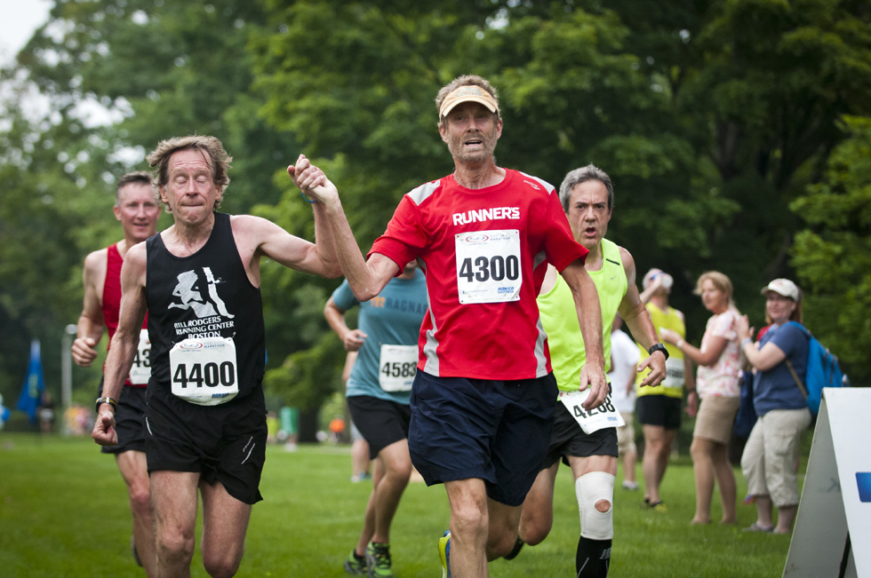 2013.06.30 - Middletown, CT - Running legends Bill Rogers and Amby Burfoot (L-R) approach the finish line of the innaugural 4-mile run holding hands. Rogers and Amby finished with a time of 31:51 for an overall 103rd place. Rogers won the Boston and New York Marathon four times each between 1975 and 1980. Burfoot won the Boston Marathon in 1986. Photograph by Mark Mirko | mmirko@courant.com