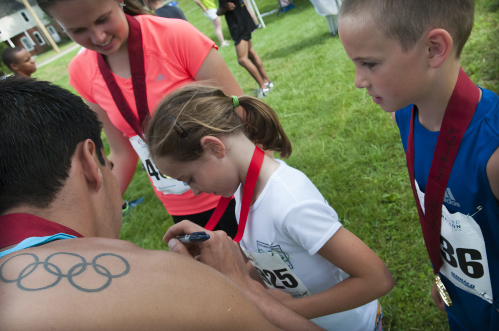 2013.06.30 - Middletown, CT - Glastonbury Olympian Donn Cabral, who won the Legends Race with a time of 0:19:28, autographs a medal ribbon 9-year-old Margaux(cq) Selfor of Old Saybrook. Selfor ran the kid's division race and four of her family members including sister Bridgid (cq) (L-R) and Conor (cq) Selfer, ran the adult race. Photograph by Mark Mirko   mmirko@courant.com
