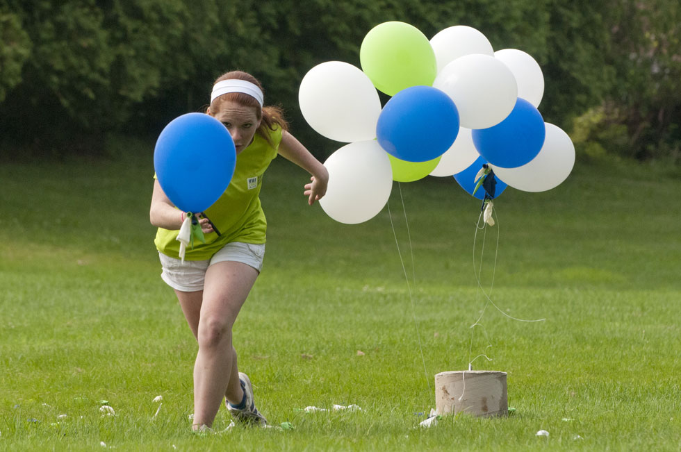 2013.06.30 - Middletown, CT - Legends Run staff Annie Bornhorst chases a loose balloon while taking down the finish line for the four-mile race. Photograph by Mark Mirko | mmirko@courant.com