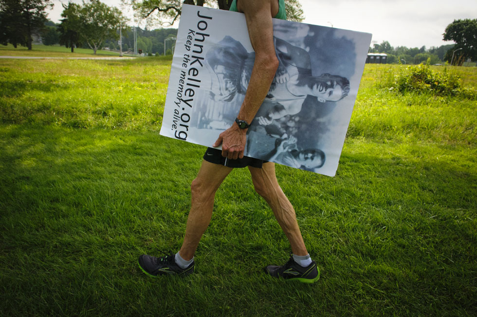 2013.06.30 - Middletown, CT - Spyros Barres, who finished first in the 50-54 year-old men's division and 12th overall in the first Legends Run, carries a poster of Hall of Fame runner and Connecticut resident John Kelley after the race. Photograph by Mark Mirko | mmirko@courant.com