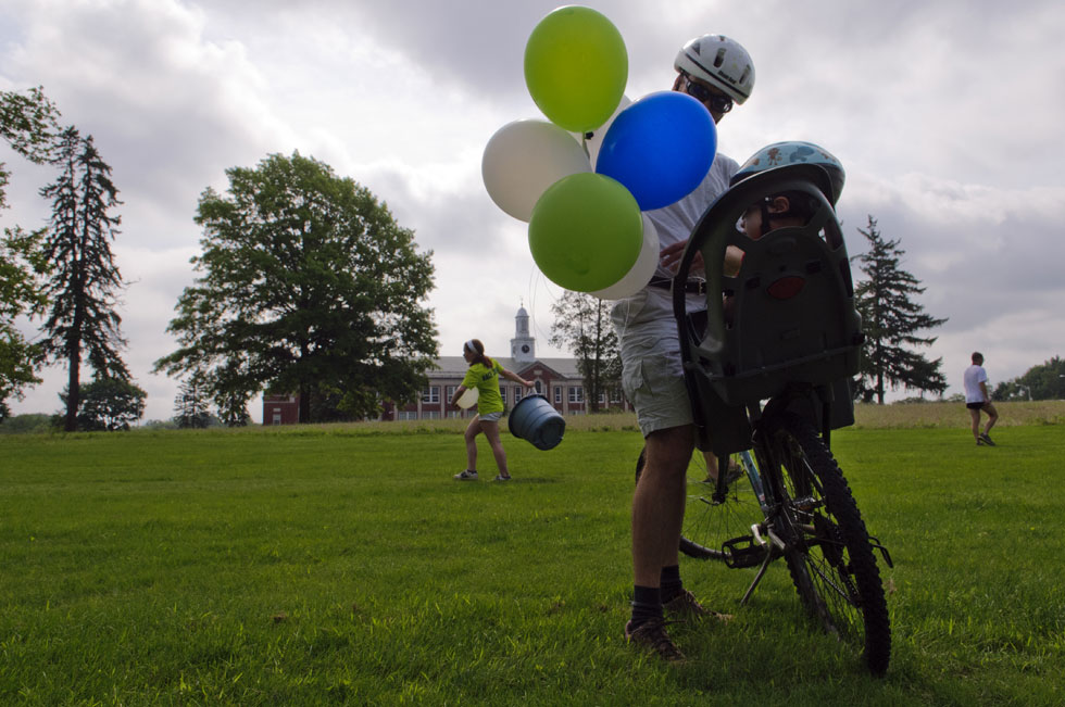 2013.06.30 - Middletown, CT - Eric Goldman ties a fisnish-line balloon to the bike seat of his son, Cyrus Leservor-Goldman after the first 4-mile Legends Run held today in Middletown. Photograph by Mark Mirko | mmirko@courant.com