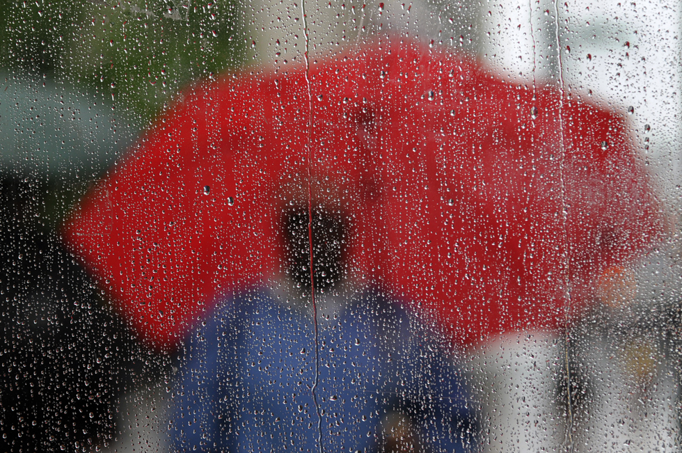 2013.06.07 - Hartford, CT - A man stands outside a rain-streaked bus shelter in front of the Old State House on Main Street in Hartford holding a red umbrella as Storm Andrea's heavy rains fall Friday afternoon.