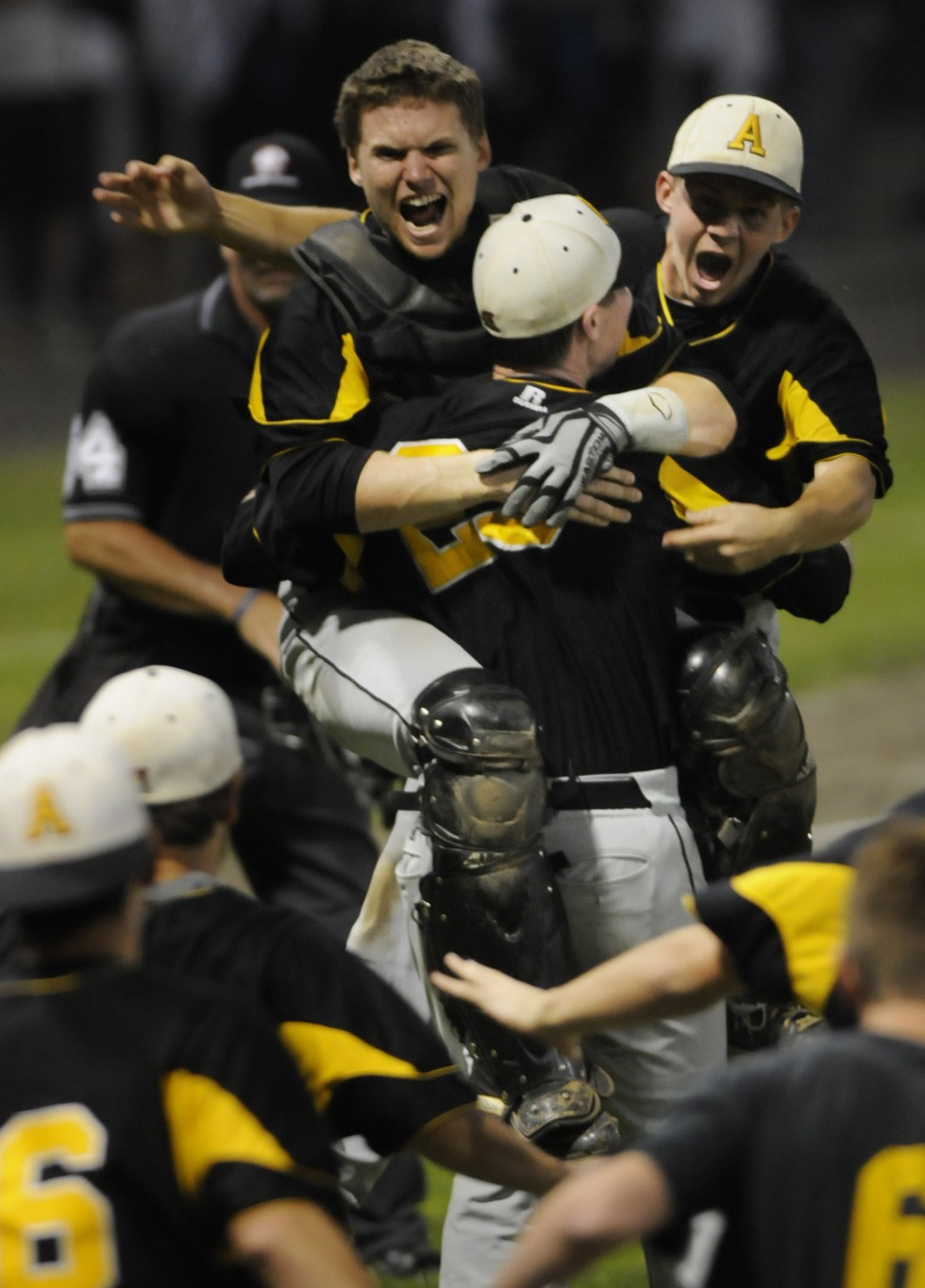 Amity catcher, Christopher Cimmino, 7, left, and third baseman, Keith Klebart, right, jump on winning pitcher Michael Concato after the win. Amity High School beat Southington High School in the CIAC Class LL Baseball Championship in a game played at Palmer Field in Middletown by a score of 4 to 0.