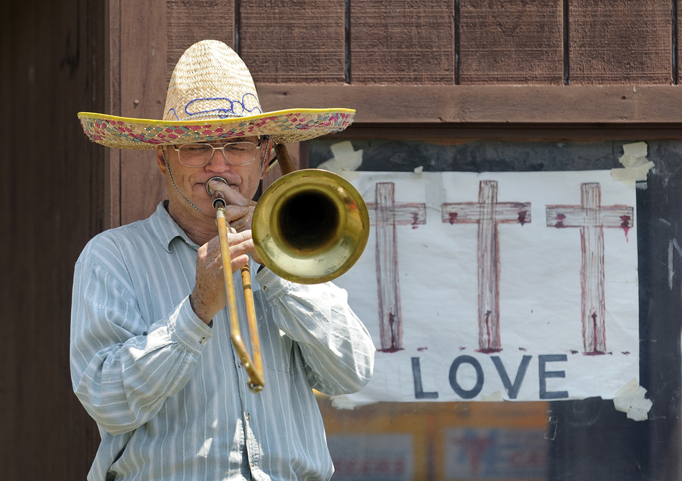 "2013.06.24 - Tolland, CT - Jim Sumner, of Tolland, plays the hymn ""How Great Thou Art"" on the trombone while standing next to a shelter at a commuter parking lot off I-84 in Tolland. A retired auto-body repairman, Sumner said he was reborn about 35 years ago and feels compelled to evangelize.  He plays one of three horns he brings to the parking lot about once or twice a week when ""the spirit moves me,"" he said. He taped up a drawing he did of three crosses inside the shelter window.  He plays to encourage people in faith and to reach out to people that don't have any, he explained.  ""The lonely and the broken-hearted people are my biggest concern,"" he said.  CLOE POISSON