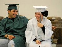 Hartford Culinary Arts Academy classmates Jose Rodan, 19, (from left) and Bryanna Moreno, 18, enjoy a few laughs together while waiting to line up for their commencement procession into the Weaver High School auditorium.