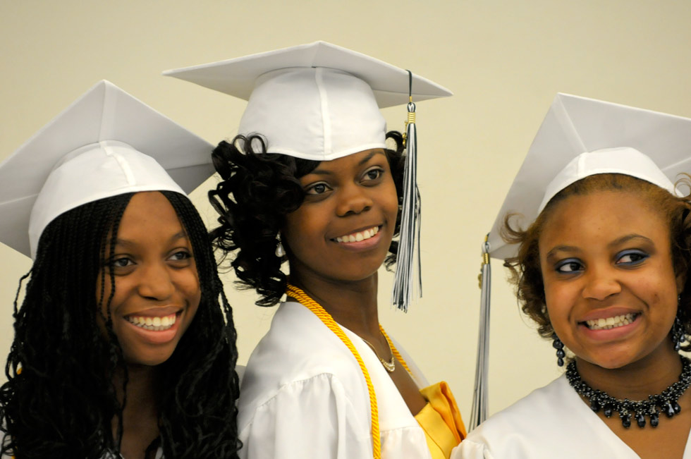 Alicia Hollingsworth, 18, (from left), D'Briana Gopaul, 19, and Shakara Jewell, 18, pose for a quick photograph before lining up for their commencement procession at Weaver High School on Thursday morning.