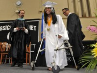 2013.06.15 - Hartford,CT - Graduating senior Jacqueline Santiago walks in front of a crowd for the first time to receive her diploma at Classical Magnet School graduation Saturday. Santiago has cerebral palsy.  Awaiting the diploma presentation at left it principal James I. Motes. BRAD HORRIGAN | bhorrigan@courant.com