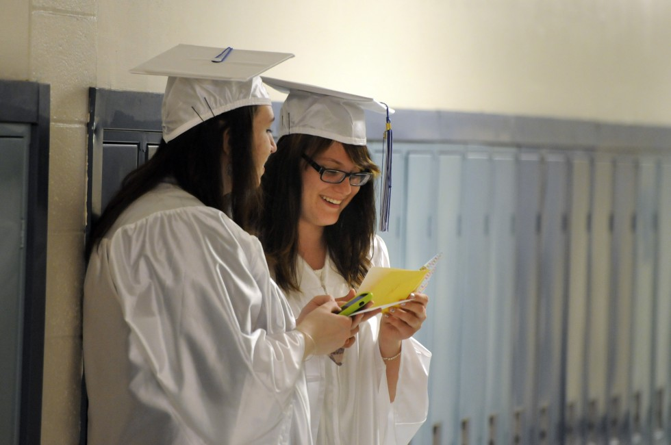 Savannah Kelly, 18, left, looks on as Vanessa Kania, 17, reads a note she received from her Latin teacher before the ceremony. Kelly said she plans to travel after graduation, and Kania, said she plans to attend UConn.