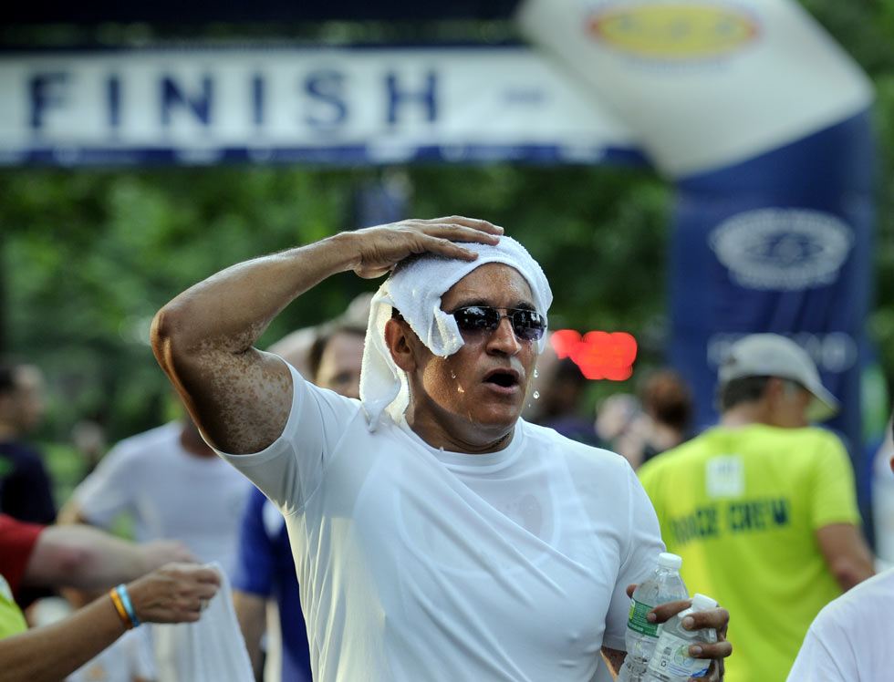 Manny Sandoval of New Britain soaks his head with a cold towel after crossing the finish line with the temperatures near 100 degrees Thursday night.