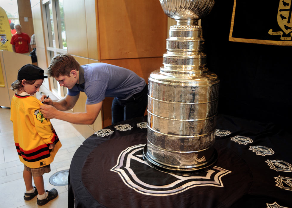 With the Stanley Cup on display close by, Chicago Blackhawks player, Ben Smith signs the jersey of Austin Renggli, 7, of W. Suffield during an event at the Westminster School Tuesday.