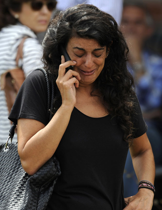 A relative of one of the victims of the train crash cries as she speaks on the phone.  REUTERS/Eloy Alonso