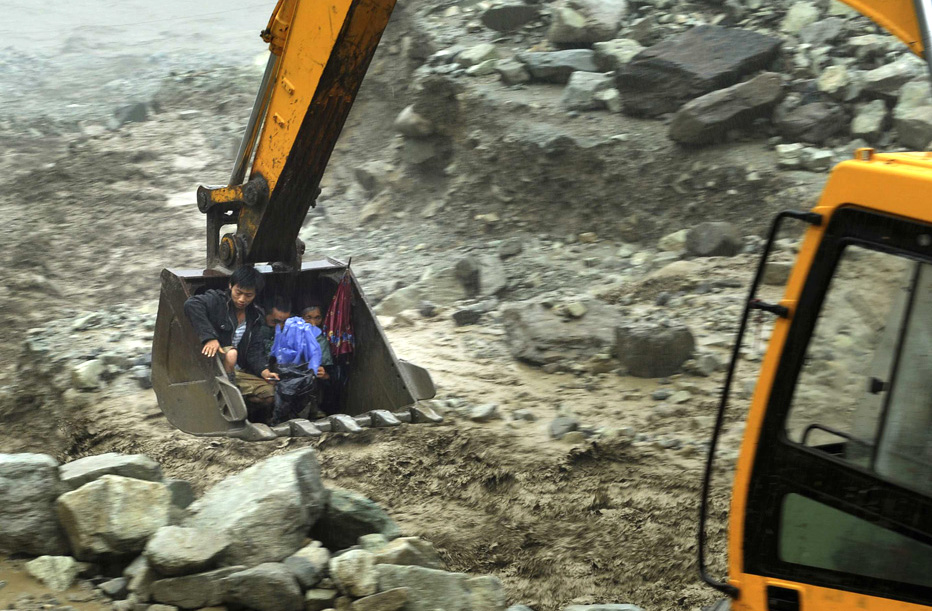 An excavator moves villagers away from a flooded area during heavy rainfall in the Sichuan province of China. More than 300 hundred people were evacuated after roads connecting the township to the outside were cut off by floods and landslides. REUTERS/Stringer