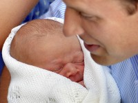 Britain's Prince William holds his newborn son outside of St Mary's Hospital before leaving with Kate, who gave birth to the couple's first child. The baby is third in line to the British throne.REUTERS/John Stillwell/POOL