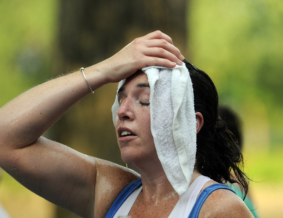 Colleen Borawski of E. Windsor soaks her head with a cold towel after crossing the finish line with the temperatures near 100 degrees.