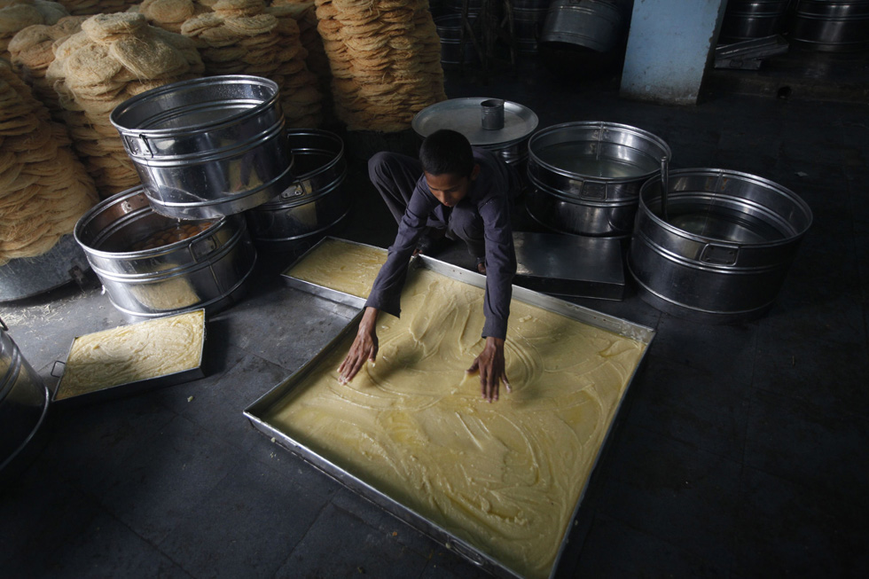A baker prepares 'khajla', a popular sweet dish, ahead of the holy month of Ramadan in Karachi, Pakistan, July 9, 2013. REUTERS/Athar Hussain