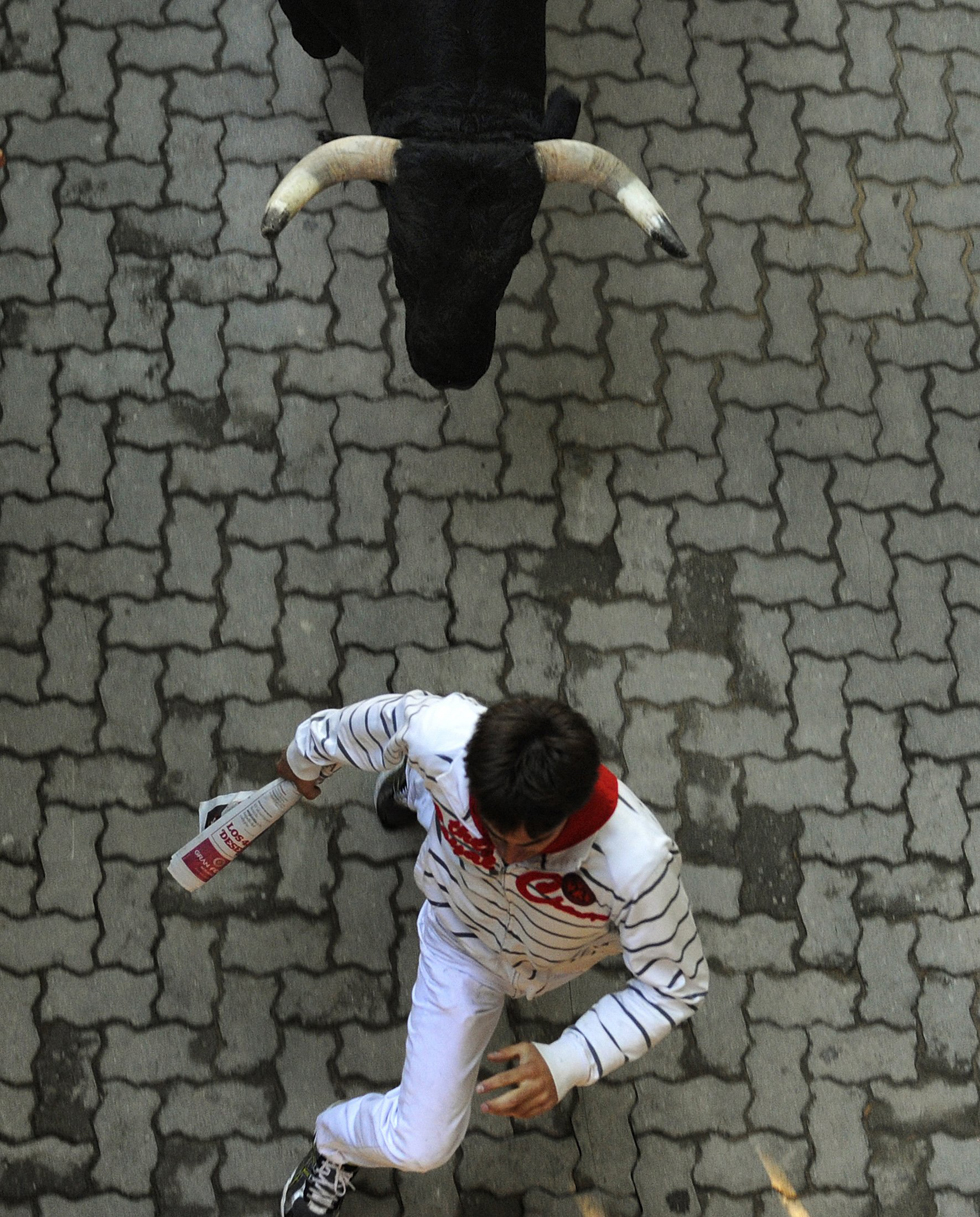 A runner sprints in front of a bull at the entrance to the bull ring during the second running of the bulls of the San Fermin festival in Pamplona July 8, 2013. REUTERS/Eloy Alonso