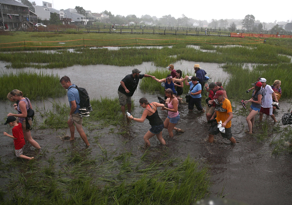 People cross the marsh in the pouring rain after watching wild ponies during their annual swim from Assateague Island to Chincoteague Island in Virginia. (Photo by Mark Wilson/Getty Images)