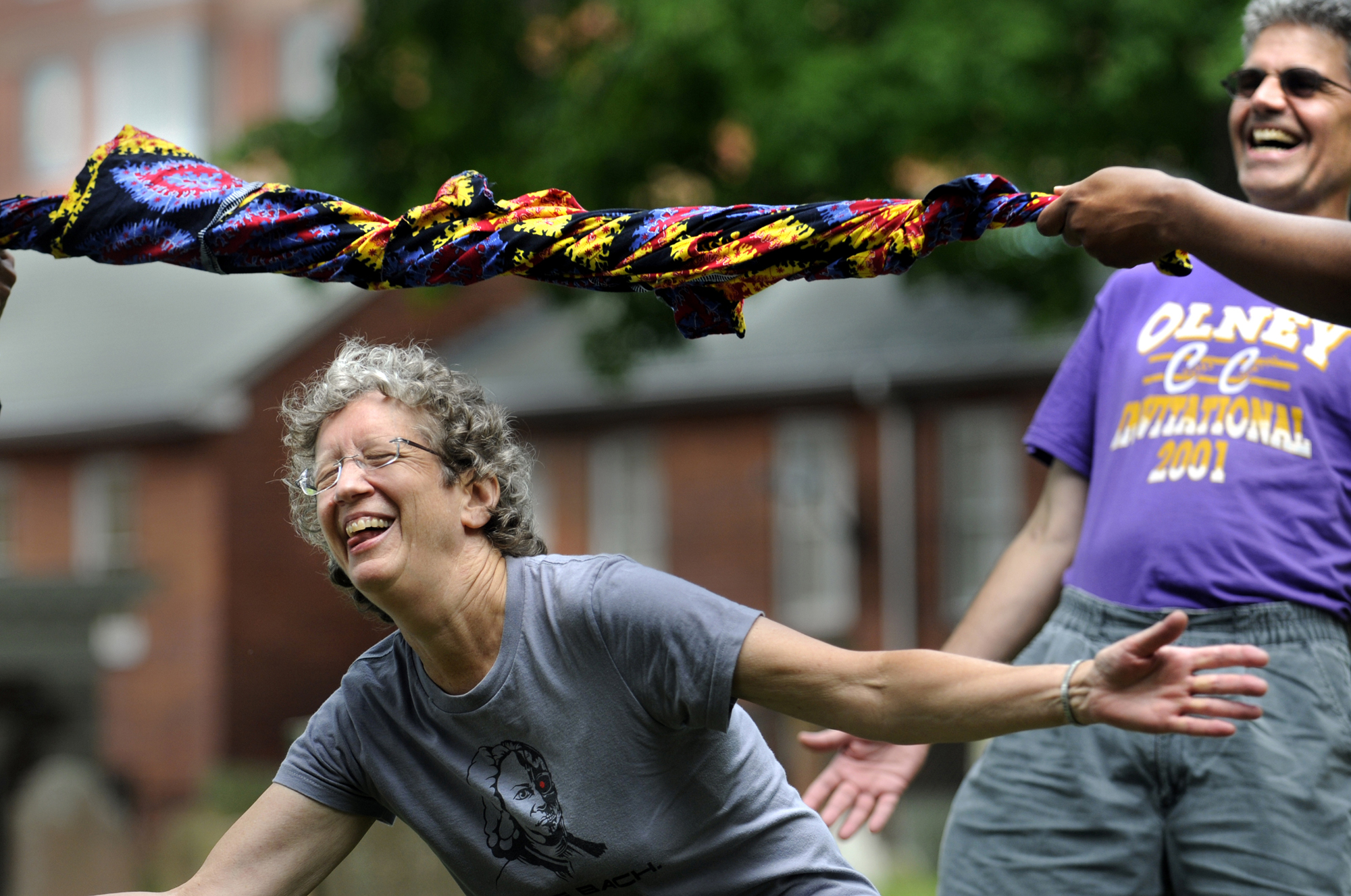 Using traditional African fabric as the bar, Ginny Allen of West Hartford performed the limbo the best she could during a program at the Ancient Burying Ground. At right is Zean Gassmann of Canton.