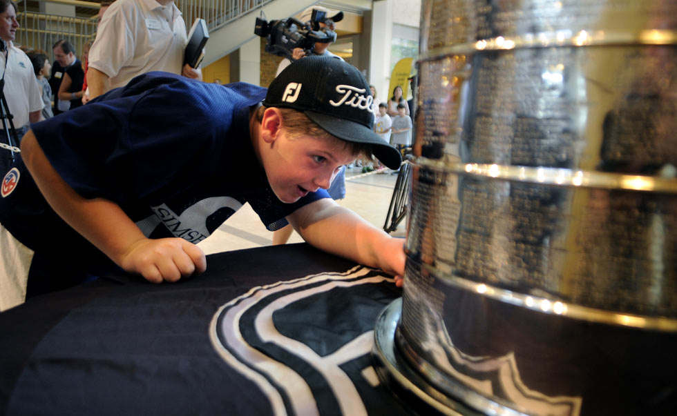 Patrick Hunt, 9, of Canton searches for his favorite player's name inscribed on the Stanley Cup during an event at the Westminster School Tuesday.