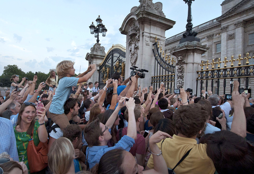 Crowds clamor to take pictures as an easel announcing the birth of Prince William and Catherine, Duchess of Cambridge's baby boy, is placed in the forecourt of Buckingham Palace in Lomdon on July 22, 2013. The to a baby boy, who will one day be heir to the British throne, AFP PHOTO/WILLOLIVER/AFP/Getty Images