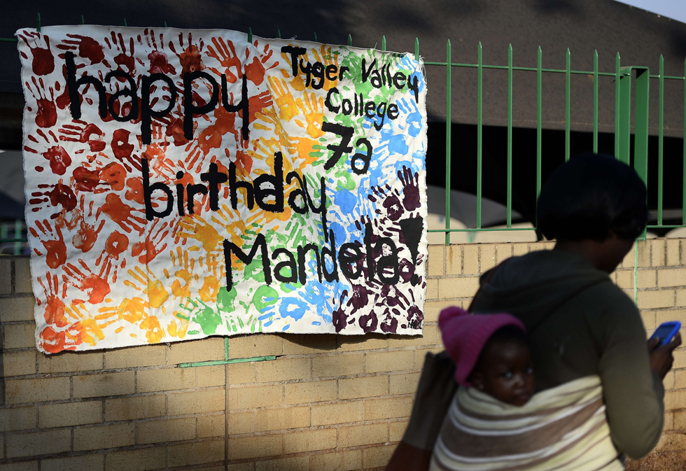 "A woman walks past a happy birthday banner for former South African President Nelson Mandela on July 18, 2013 outside the Medi Clinic Heart Hospital in Pretoria, where the anti-apartheid legend is spending his 95th birthday. Children in schools around the country kicked off the celebrations by singing ""Happy Birthday"" to Mandela, on a day that also marked the 15th anniversary of his marriage to third wife Graca Machel.The United Nations declared the Nobel Peace laureate's birthday Mandela Day in 2010, but for many this year it takes on extra poignancy. AFP PHOTO/STEPHANE DE SAKUTIN/AFP/Getty Images"