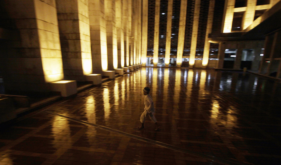 A young Muslim runs as he enters a mosque, July 9, 2013, in Jakarta, Indonesia. Muslims must fast in the month of Ramadan from dawn until sunset, when they break the fast with the meal known as Iftar.  (Photo by Syamsul Bahri Muhammad/Getty Images