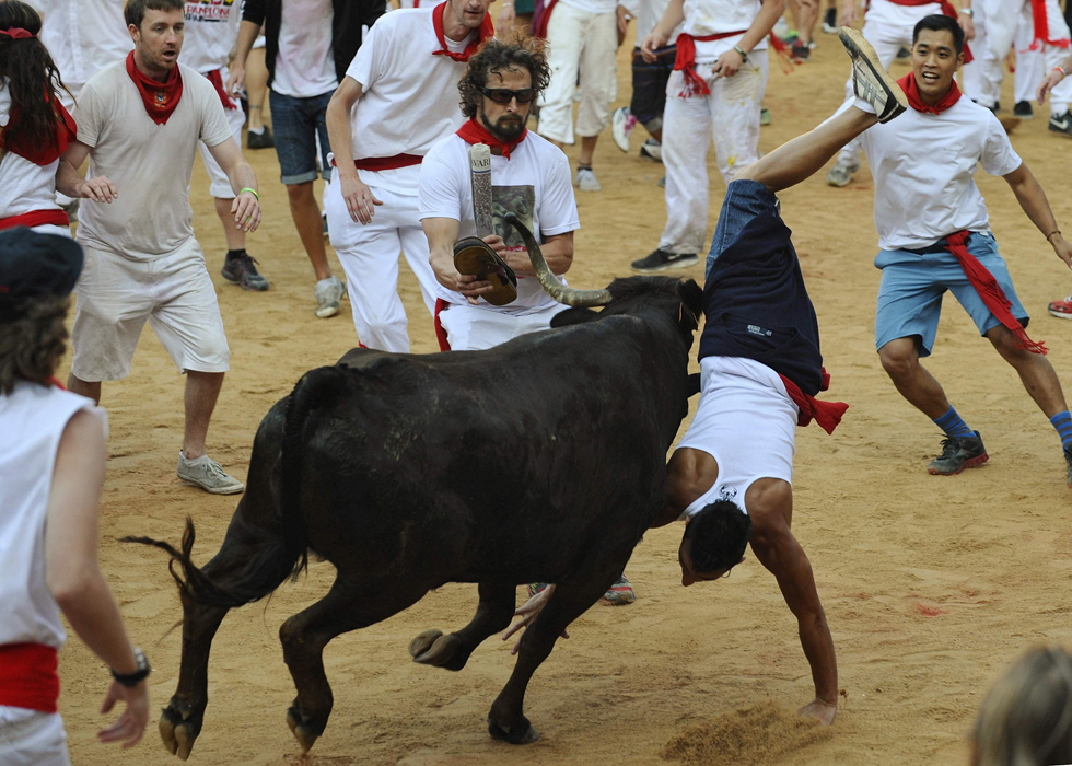 A runner gets tossed by a bull at the Running of the Bulls during the San Fermin festival in Pamplona, Spain, July 8, 2013. Several runners suffered light injuries in a run that lasted two minutes and twenty five seconds, according to local media. REUTERS/Eloy Alonso