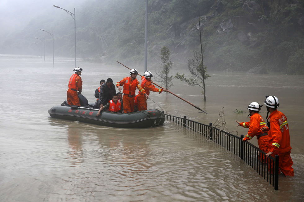 Rescuers look for victims as heavy flood waters sweep through southwest China's Sichuan province. AFP PHOTO/AFP/Getty Images