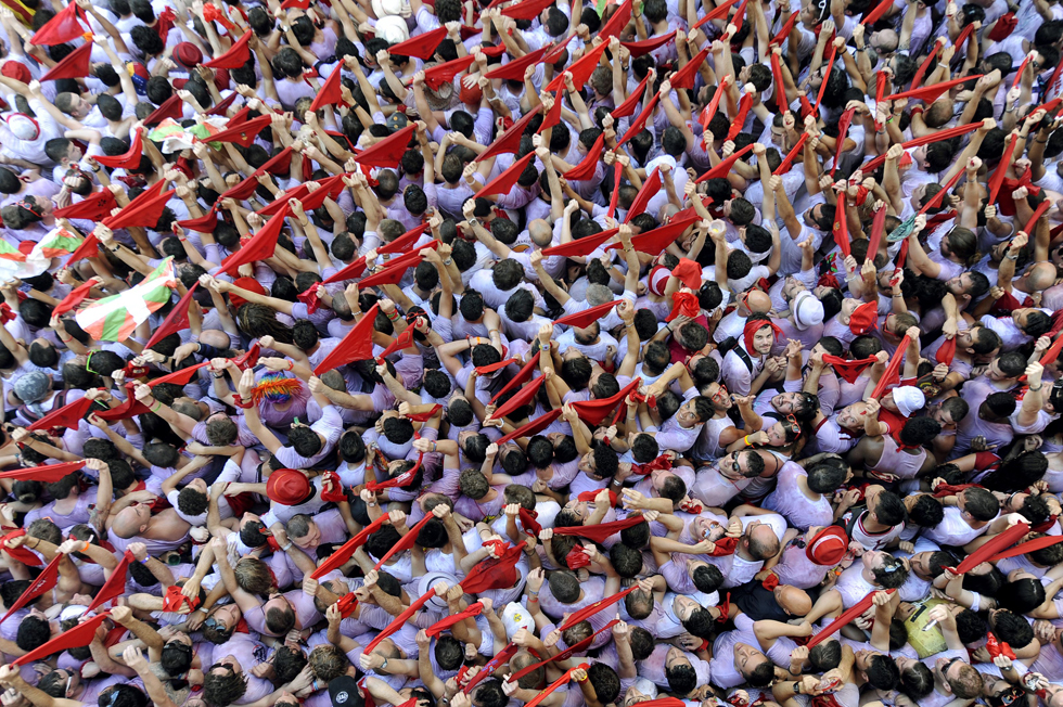 Participants with red scarves celebrate during the 'Chupinazo' marking the start of the San Fermin Festival, July 6, 2013, in front of the Town Hall of Pamplona, Spain. A red-and-white ocean of fans erupted in cheers to launch Spain's annual San Fermin bull-running festival. AFP PHOTO/ RAFA RIVAS/AFP/Getty Images