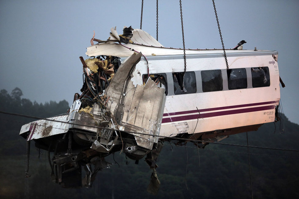 A crane removes a carriage from the tracks at the crash site. REUTERS/Miguel Vidal