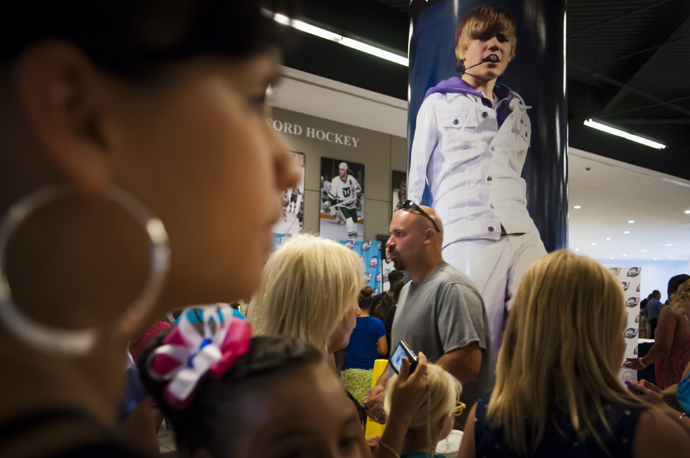 2013.07.18 - Hartford, CT - People mill past Hartford Whalers photographs and a larger than life image of teen idol Justin Bieber beofre the sart of Bieber's XL Center concert. Photograph by Mark Mirko | mmirko@courant.com