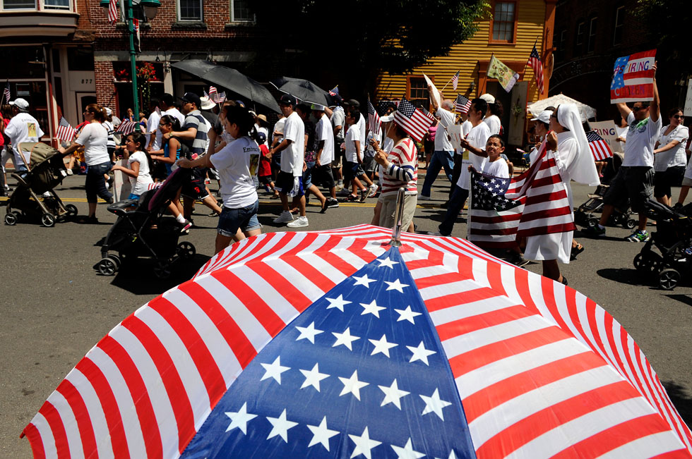 The parade has always drawn a rather diverse crowd and this year was no different. A group of immigrants carrying the American Flag and signs of Aspiring Citizen marched past an umbrella with an American Flag design.