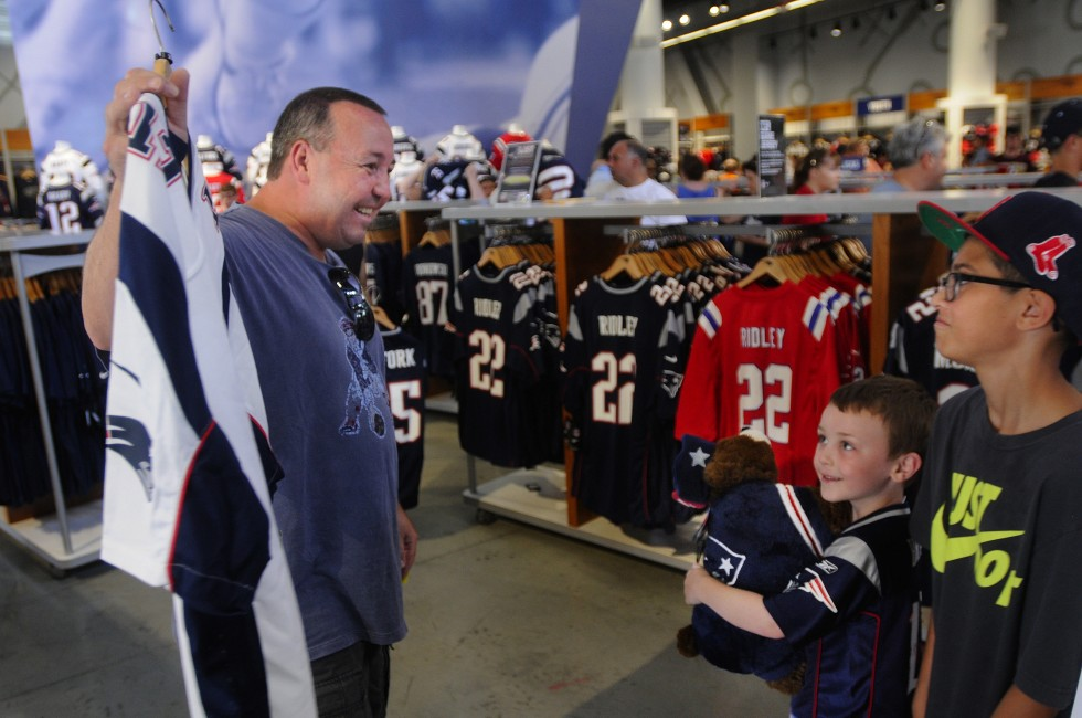 Mike Peters, of Arlington Heights Illinois, shows his sons, Joe, 5, and Ryan 12, his pick to replace the Hernendez Jersey he just exchanged. Ryan, was not impressed because they already have a few Brady Jersey's.The Peters family, was heading back home to Illinois, from a vacation in Quincy, where the elder Peters grew up.
